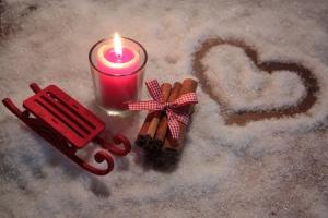 Schlitten und Kerze im Schnee